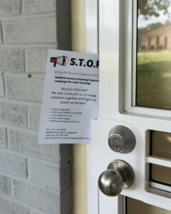 A flyer from the Bedford County Listening Project on a screen door