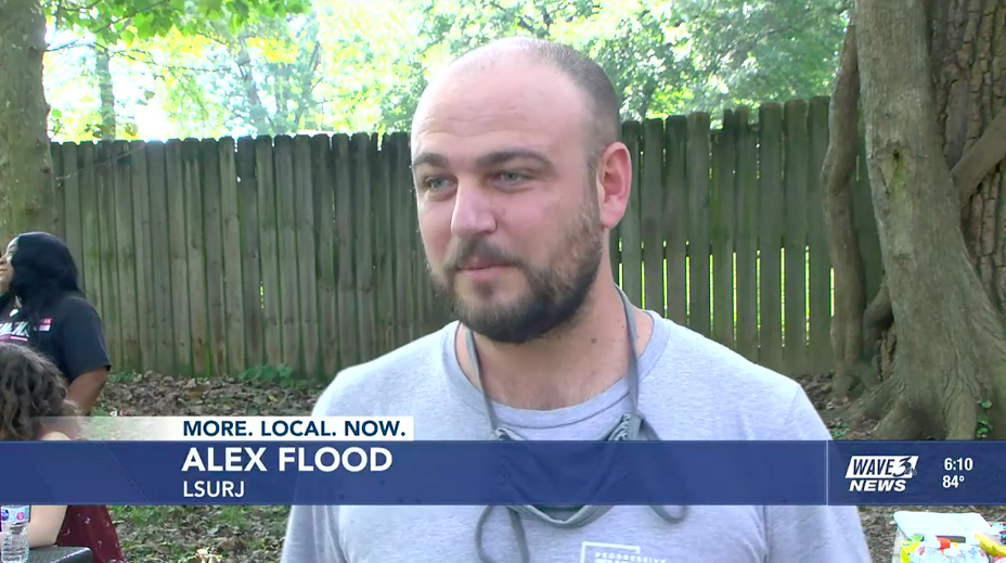 image in a screen shot of an interview with local LSURJ member Alex Flood. The image shows a white man with a short beard, wearing a tshirt, with a mask around his neck, talking to the camera. He is outside and there is a fence in the background.