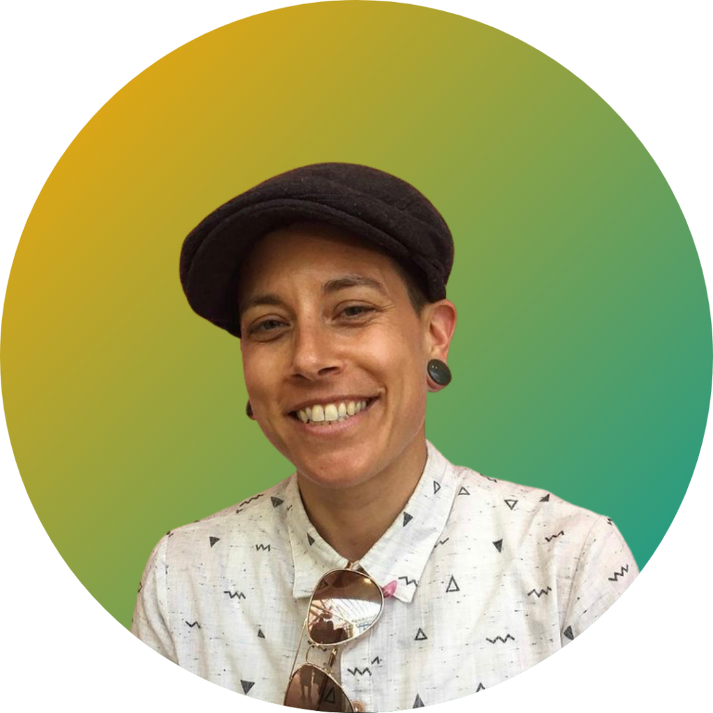 Image shows a white nonbinary person smiling in front of a yellow-green gradient background. They are wearing a white button up shirt with a small black print, plugs in their ears, sunglasses hanging from their shirt and a black newsboy cap.