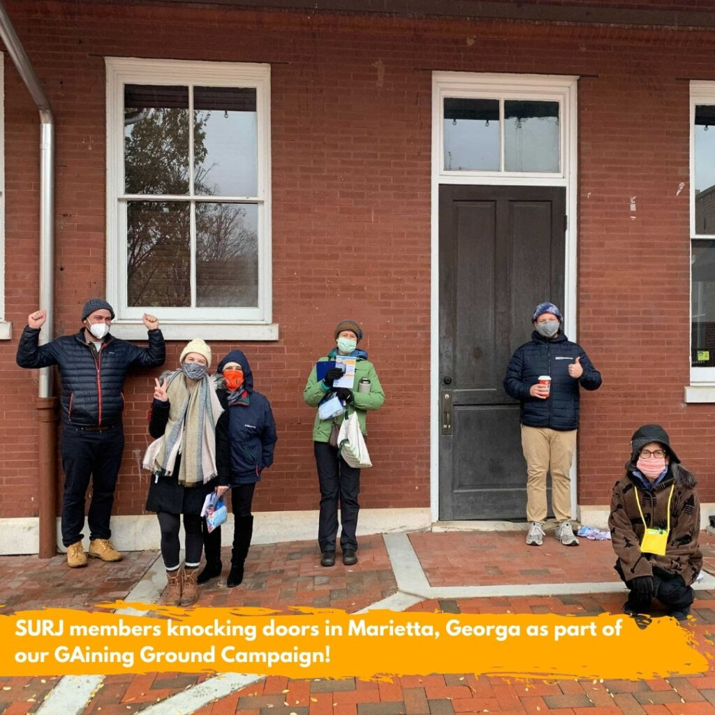 """Image shows a group of 6 white folks, bundled up and wearing masks, outside a red brick building, holding canvassing literature. The text overlaid on the image reads: """"SURJ members knocking doors in Marietta, Georgia as part of our GAining Ground campaign."""""""