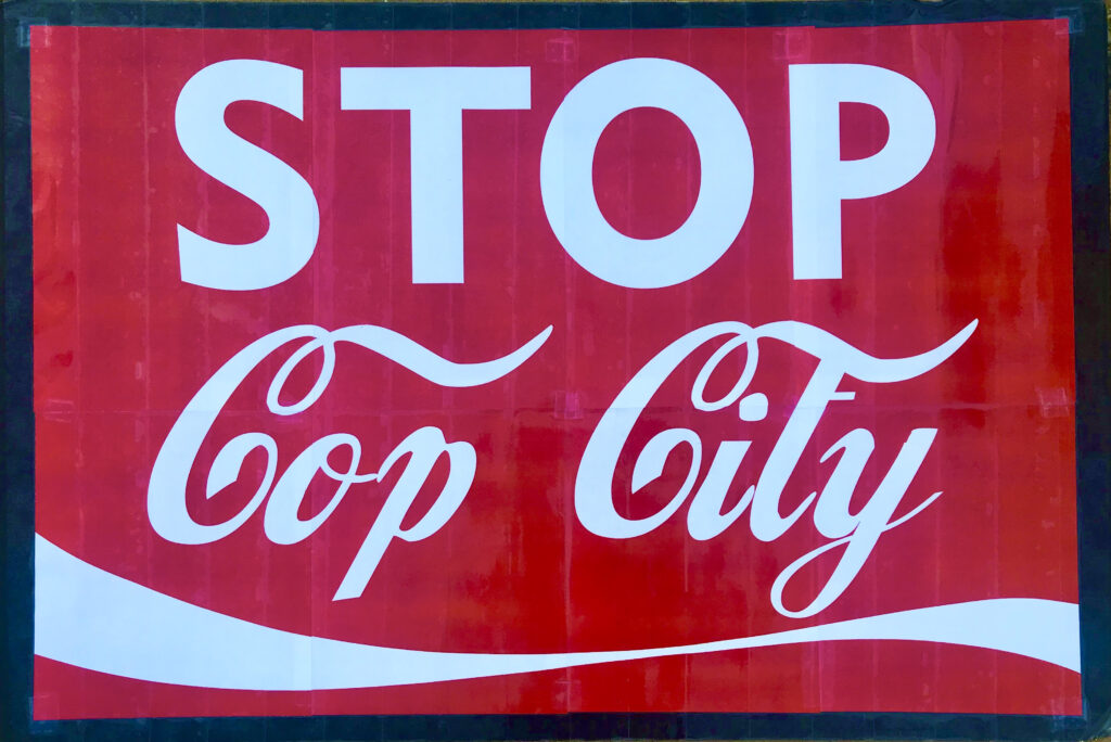 """image shows a sign that reads """"stop cop city"""" in the font and style of the Coca Cola logo"""