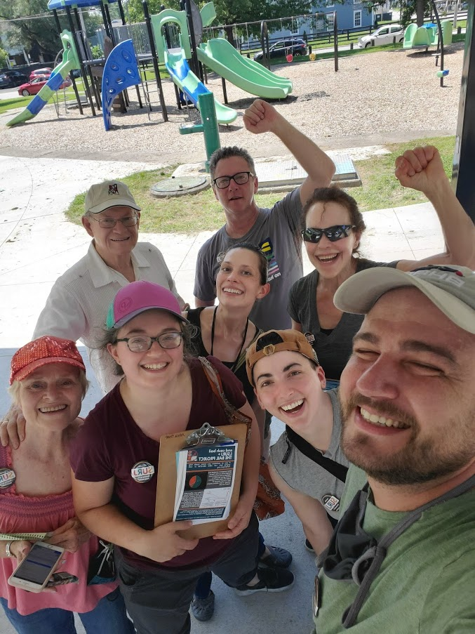 image shows a group of white folks in a park posing for a selfie. One of them is holding a clipboard with canvassing literature.